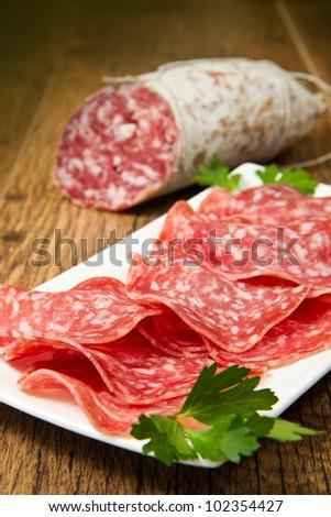 Salami sliced on wood background - stock photo