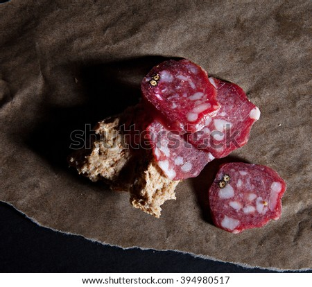 salami with nuts on a greaseproof paper with a beautiful light with shadows - stock photo