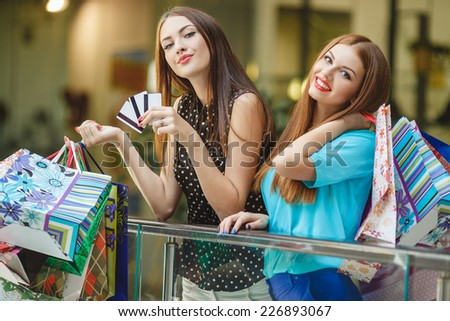 sale and tourism, happy people concept - beautiful women with shopping bags and credit card in the ctiy - stock photo