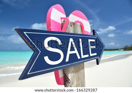 SALE arrow on the beach - stock photo