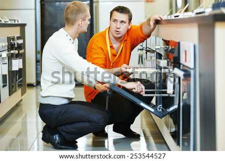 Sale assistant demonstrating cooker stove to young family in home appliance shopping mall supermarket - stock photo