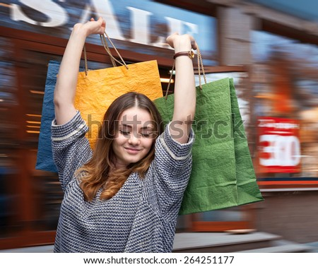 Sale. Beautiful young woman with shopping bags against the mall on the background - stock photo