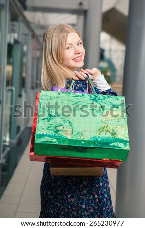 sale concept. beautiful young woman with a shopping bags in the mall - stock photo