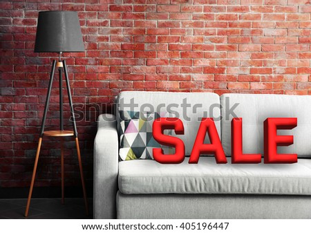 Sale concept. Grey sofa and floor lamp against brick wall in the room - stock photo