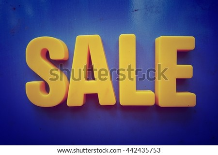 Sale concept. Yellow letters on blue background - stock photo