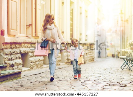 sale, consumerism and people concept - happy mother and child with shopping bags walking along city street - stock photo