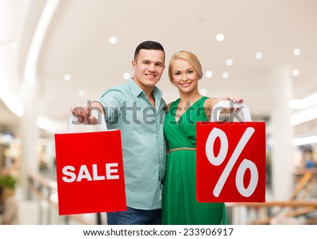 sale, consumerism and people concept - happy young couple with red shopping bags in mall - stock photo