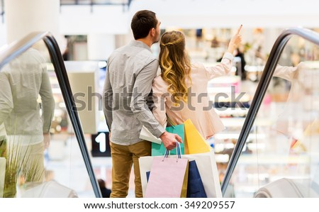 sale, consumerism and people concept - happy young couple with shopping bags going down by escalator and pointing finger in mall - stock photo