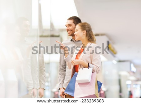 sale, consumerism and people concept - happy young couple with shopping bags pointing finger to shop window in mall - stock photo