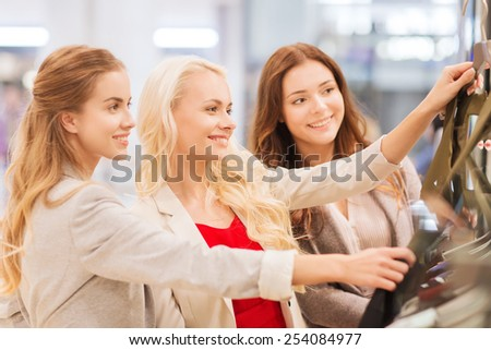 sale, consumerism and people concept - happy young women choosing clothes in mall - stock photo