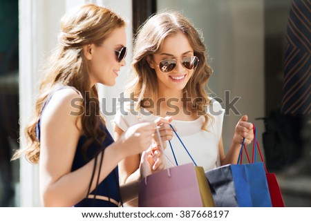 sale, consumerism and people concept - happy young women looking into shopping bags at shop window in city - stock photo