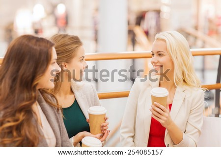 sale, consumerism and people concept - happy young women with shopping bags and coffee paper cups in mall - stock photo