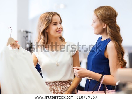 sale, consumerism and people concept - happy young women with shopping bags choosing clothes at clothing shop - stock photo