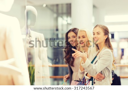 sale, consumerism and people concept - happy young women with shopping bags pointing finger to shop window in mall - stock photo