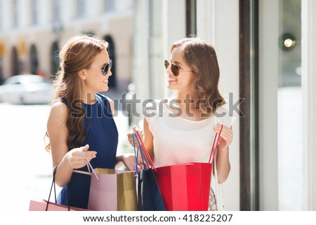 sale, consumerism and people concept - happy young women with shopping bags talking at shop window in city - stock photo