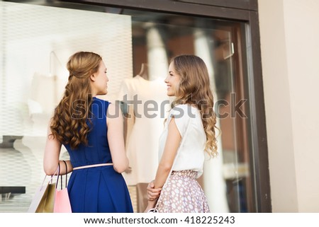 sale, consumerism and people concept - happy young women with shopping bags talking at to shop window in city from back - stock photo