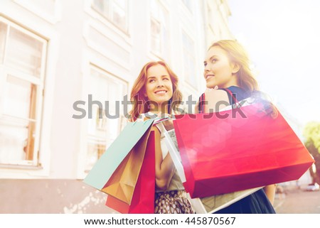 sale, consumerism and people concept - happy young women with shopping bags walking along city street and looking back - stock photo