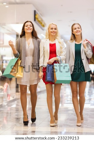sale, consumerism and people concept - happy young women with shopping bags walking in mall - stock photo
