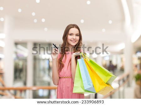 sale, consumerism, money and people concept - happy young woman with shopping bags and credit card in mall - stock photo