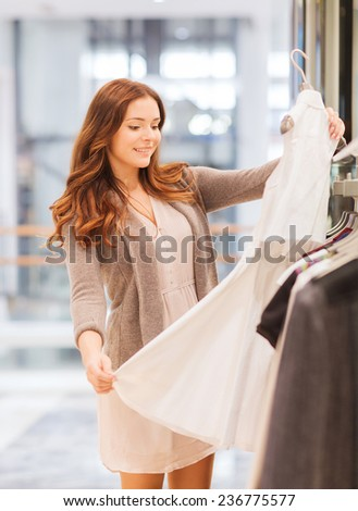 sale, consumerism, shopping and people concept - happy young woman choosing clothes in mall - stock photo