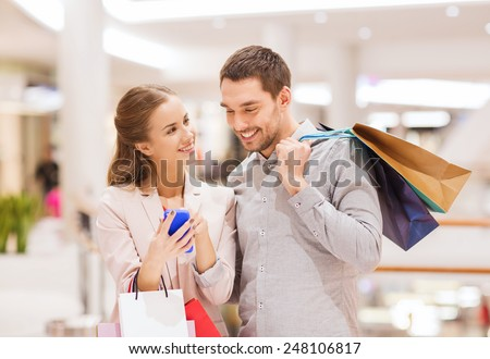 sale, consumerism, technology and people concept - happy young couple with shopping bags and smartphone talking in mall - stock photo