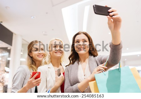 sale, consumerism, technology and people concept - happy young women with smartphones and shopping bags taking selfie in mall - stock photo