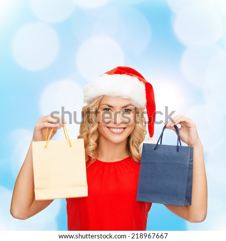 sale, gifts, christmas, holidays and people concept - smiling woman in red dress and santa helper hat with shopping bags over blue lights background - stock photo