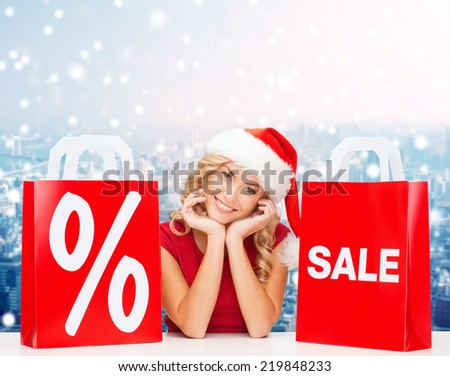 sale, gifts, christmas, holidays and people concept - smiling woman in santa helper hat with shopping bags and percent sign over snowy city background - stock photo