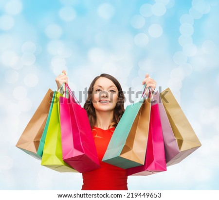sale, gifts, christmas, holidays and people concept - smiling woman with colorful shopping bags over blue lights background - stock photo