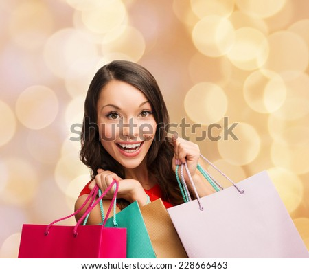 sale, gifts, christmas, holidays and people concept - smiling woman with colorful shopping bags over beige lights background - stock photo