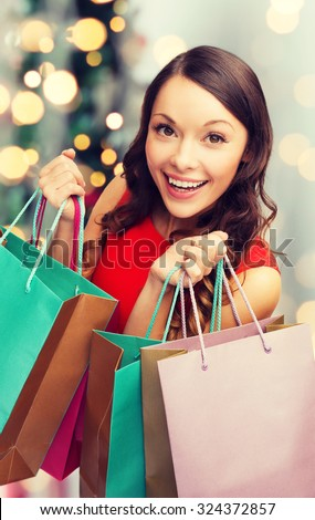sale, gifts, holidays and people concept - smiling woman with colorful shopping bags over living room and christmas tree background - stock photo
