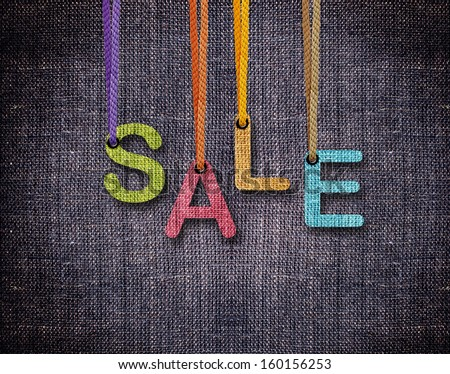 Sale letters hanging strings with blue sackcloth background. - stock photo