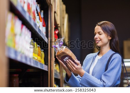 sale, shopping, consumerism and people concept - happy young woman choosing and buying bread in market - stock photo