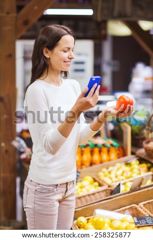 sale, shopping, consumerism and people concept - happy young woman with smartphone and tomato in market - stock photo