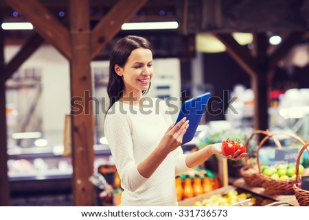 sale, shopping, consumerism and people concept - happy young woman with tomatoes and tablet pc computer in market - stock photo