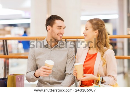 sale, shopping, consumerism, leisure and people concept - happy couple with shopping bags drinking coffee from paper cups in mall - stock photo