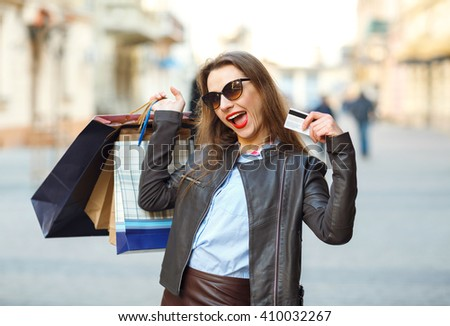 Sale, shopping, tourism and happy people concept - beautiful woman with shopping bags and credit card in the hands on a street - stock photo