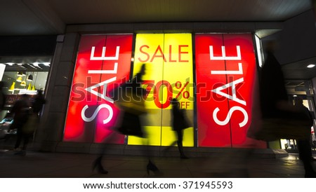 Sale signs in shop window, include silhouette of shoppers - stock photo