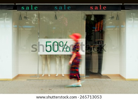 Sale signs in the shop window. Blurred figure of a woman  - stock photo