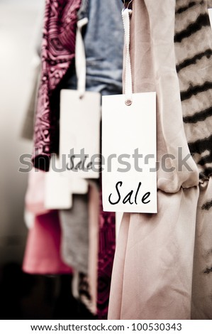 Sale tag on a rack of clothing in a women's boutique - stock photo