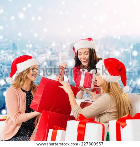 sale, winter holidays, christmas and people concept - smiling young women in santa helper hats with gifts and shopping bags over snowy city background - stock photo
