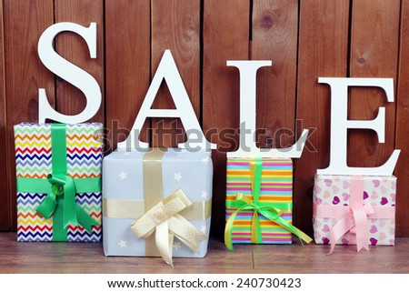 Sale with gifts on wooden background - stock photo
