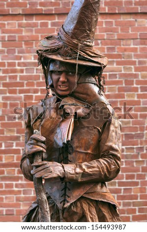 SALEM, OCTOBER 29: Woman in clothes of Witch looks at crowd in downtown Salem during the annual Halloween celebration in home of the Salem Witch Trials of 1692 -  October 29, 2009  in Salem, MA, USA - stock photo