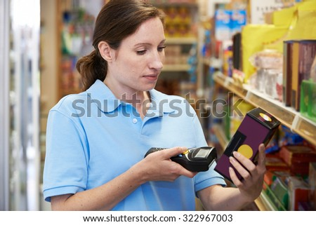Sales Assistant Checking Stock Levels In Supmarket Using Hand Held Device - stock photo