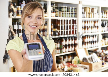 Sales Assistant In Food Store With Credit Card Machine  - stock photo