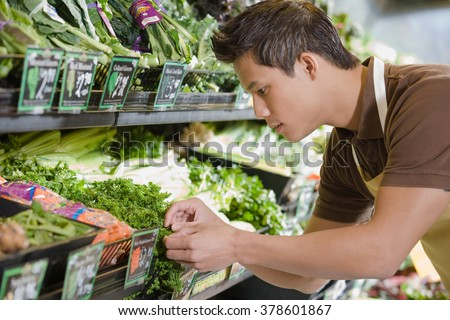 Sales assistant working in a supermarket - stock photo