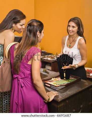 Sales clerk showing necklace to women shoppers in boutique. - stock photo