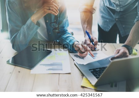 Sales Managers Working Modern Studio.Woman Showing Market Report Digital Tablet.Marketing Department Planning New Strategy.Researching Process Wood Table.Horizontal.Burred Background.Film effect - stock photo
