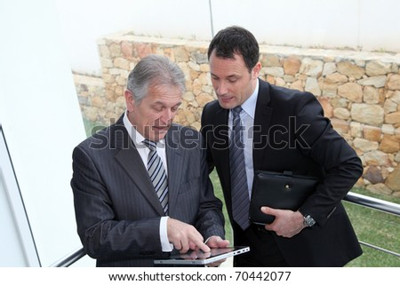 Sales people working on electronic tablet - stock photo