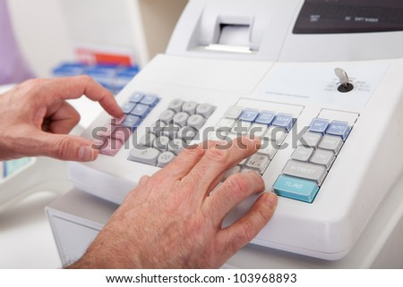 Sales person entering amount on cash register in retail store - stock photo